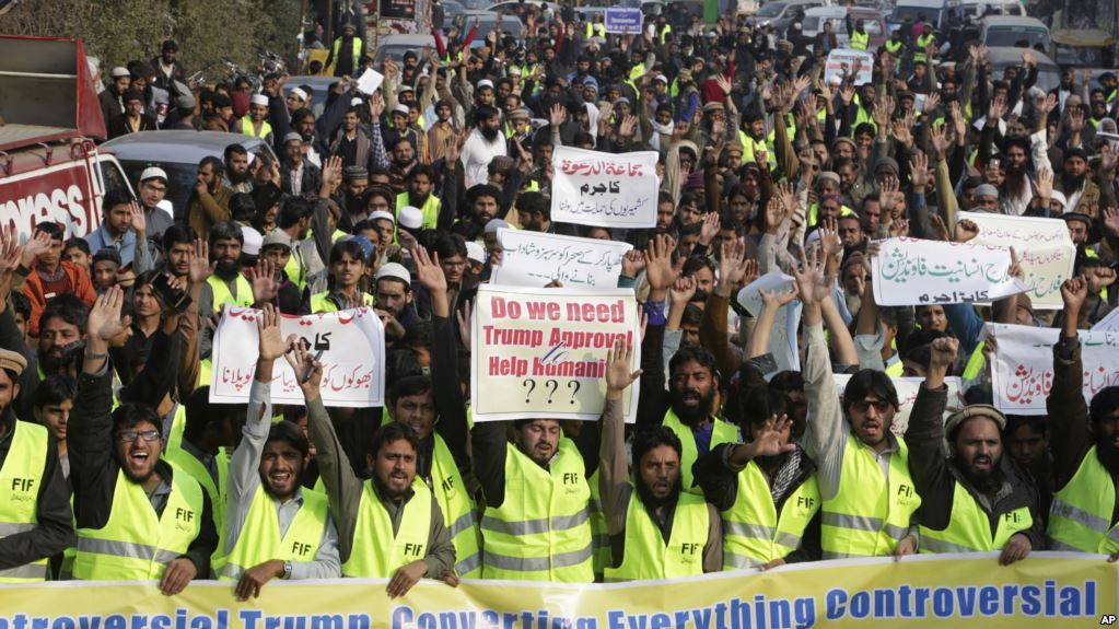 """Supporters of Pakistani religious group rally against U.S. President Donald Trump in Lahore, Pakistan, Tuesday, Jan. 2, 2018. Trump slammed Pakistan for 'lies & deceit' in a New Year's Day tweet that said Islamabad had played U.S. leaders for 'fools'. 'No more,' Trump tweeted. Placard on top reads """"Crime of Jamaat ud Dawa to support Kashmiris? """". (AP Photo/K.M. Chaudary)"""